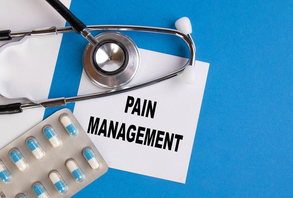 """Pain Management"""" / Schmerzbehandlung geschrieben auf blauem Ärzteordner, neben Medikamenten und Stethoskop"""