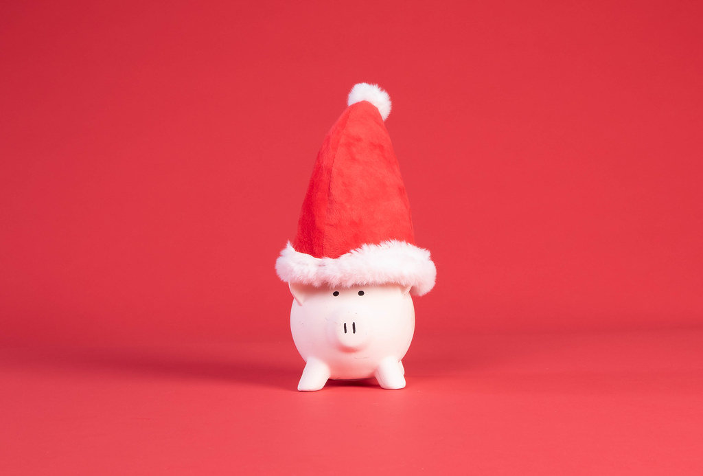 Piggy bank with Christmas hat on red background