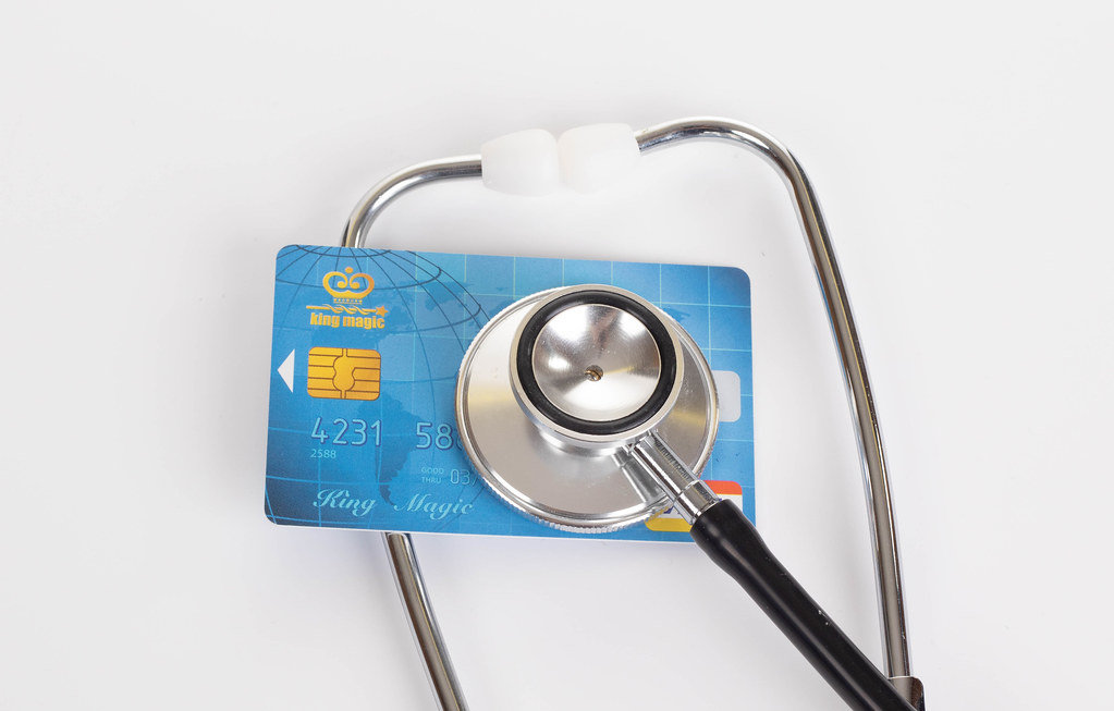 Stethoscope and Visa credit card on white background