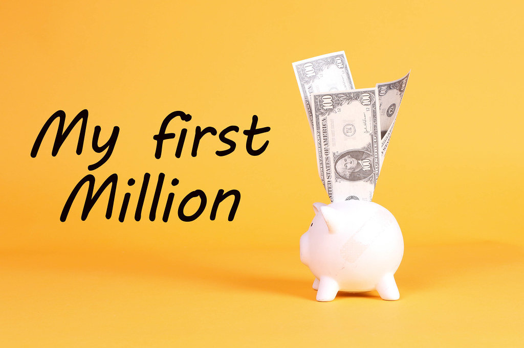 Piggy bank with dollar banknotes and My first Million text