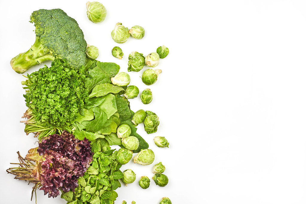 Fresh leafy greens and Brussels sprouts on white background