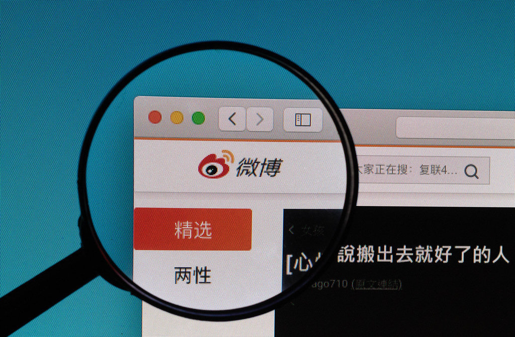 Weibo.com logo under magnifying glass