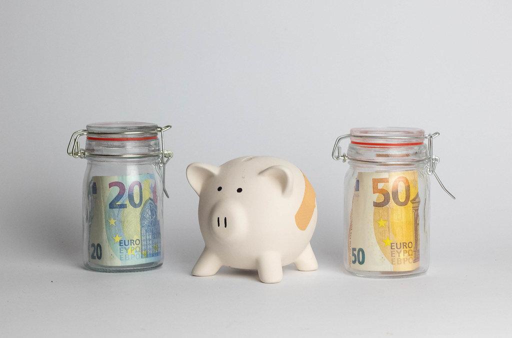 Geldsparen - Ein Sparschwein aus Porzellan und Einmachgläser mit Geldscheinen