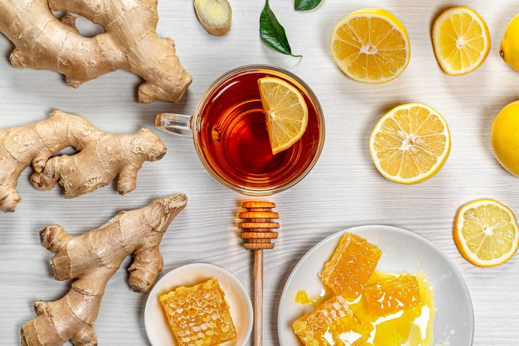 Eine Tasse Tee mit Ingwer, frischer Zitrone und Honig auf weißem Holzhintergrund - top-view