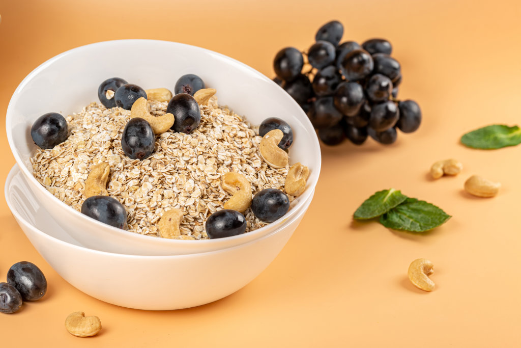 Breakfast concept, oatmeal with blue grapes and cashews