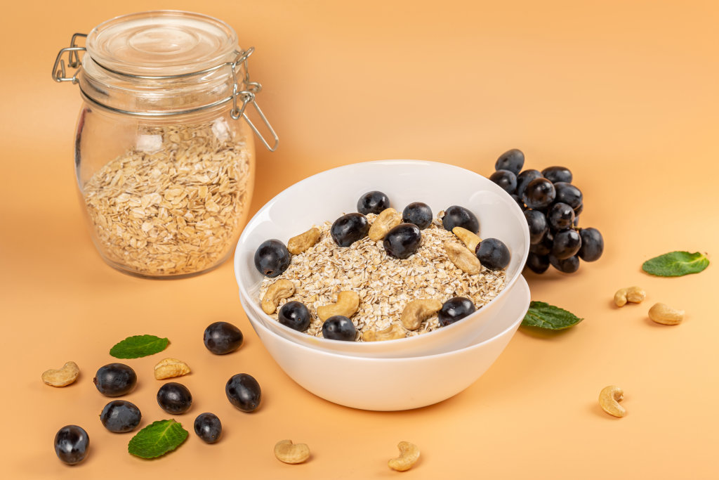 Oat flakes with grapes and cashews on an orange background with