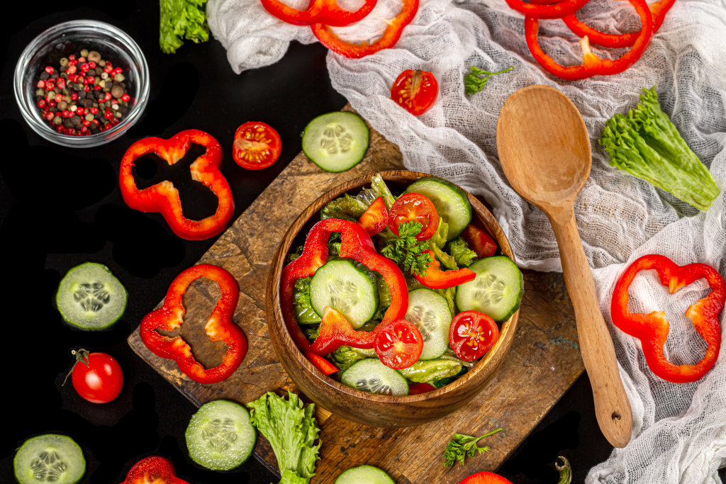 Salad with cucumbers and bell peppers in a wooden bowl, top view
