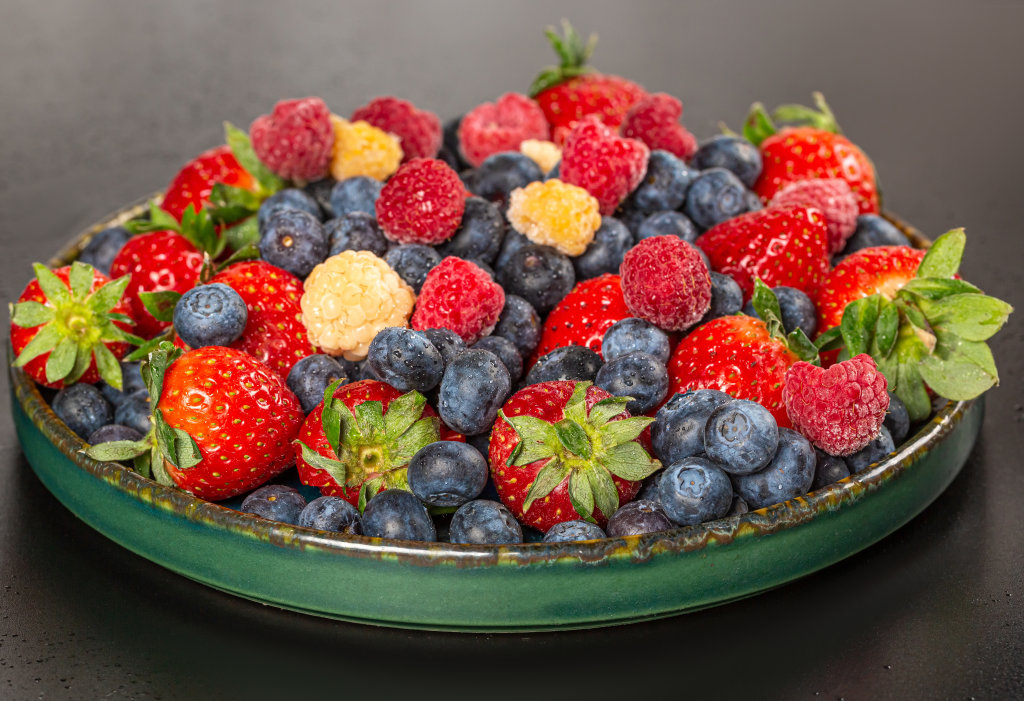 Plate with fresh strawberries, blueberries and raspberries on a