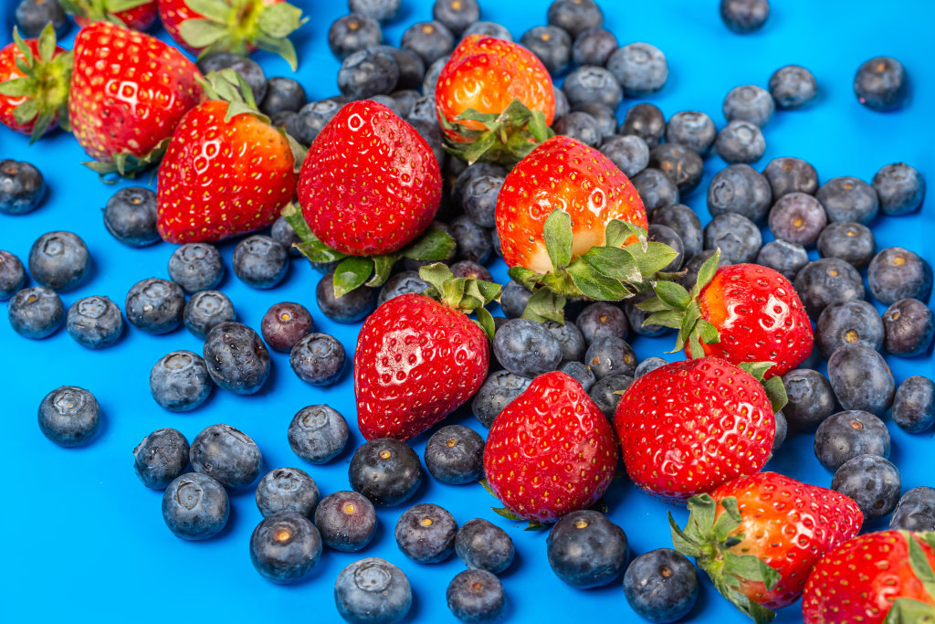 Strawberries and blueberries on a blue background