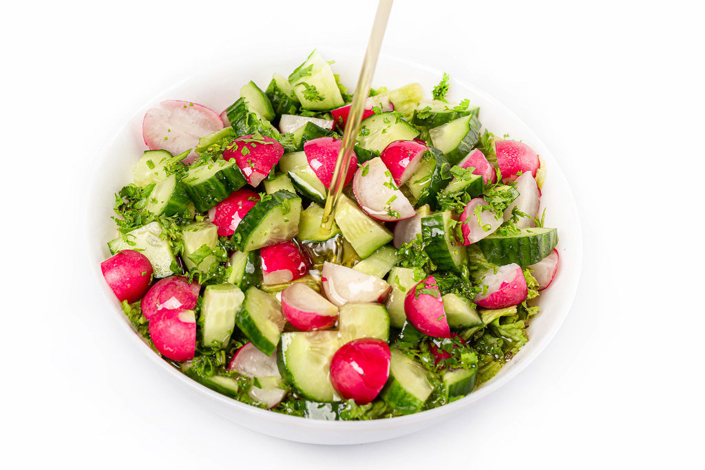 Oil is poured into a bowl of vegetable salad