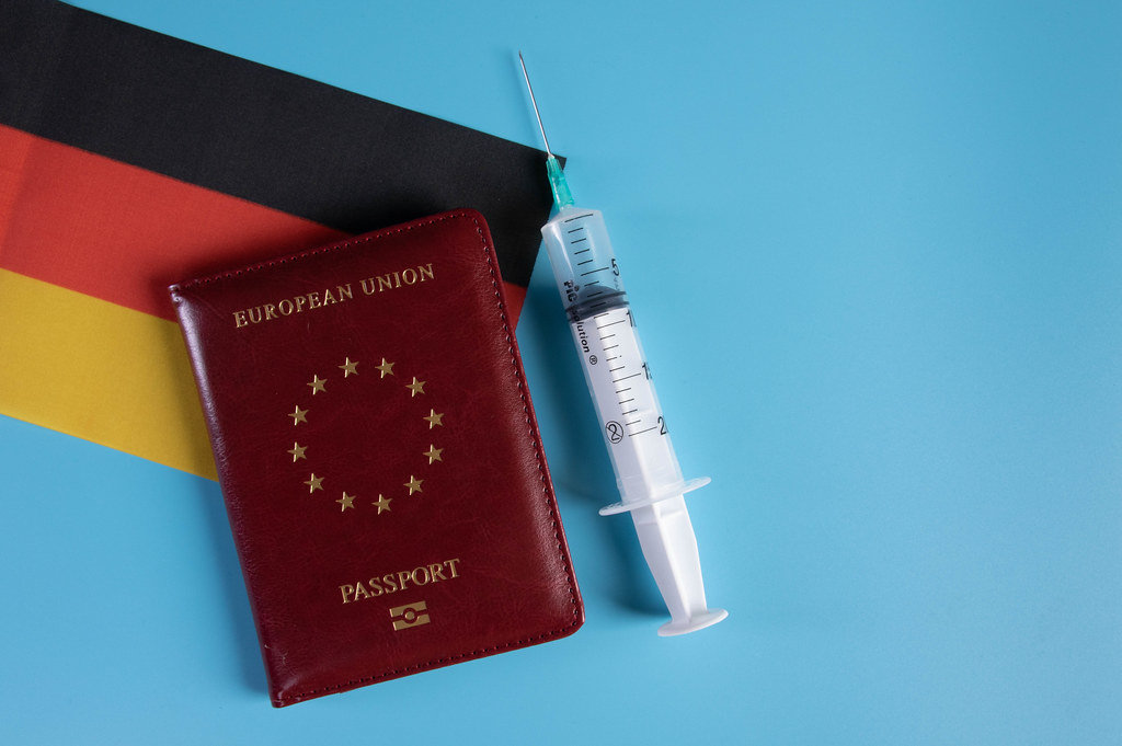 Passport with flag of Germnay and syringe on blue background