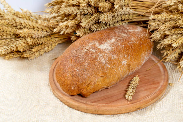 Black bread on the kitchen Board with wheat spikelets