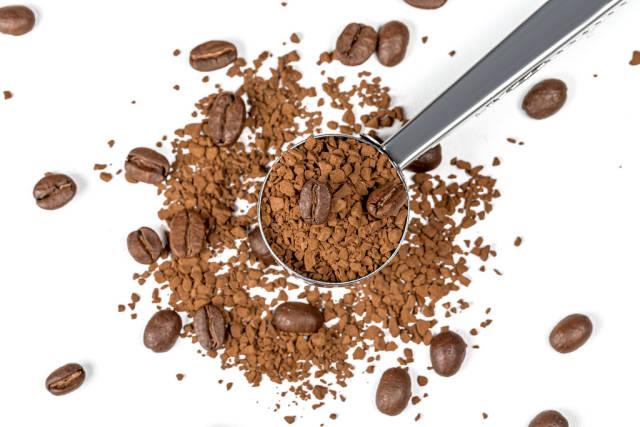 Instantkaffee mit ganzen Kaffeebohnen auf weißem Hintergrund mit eisernem Löffel. Aufnahme von oben