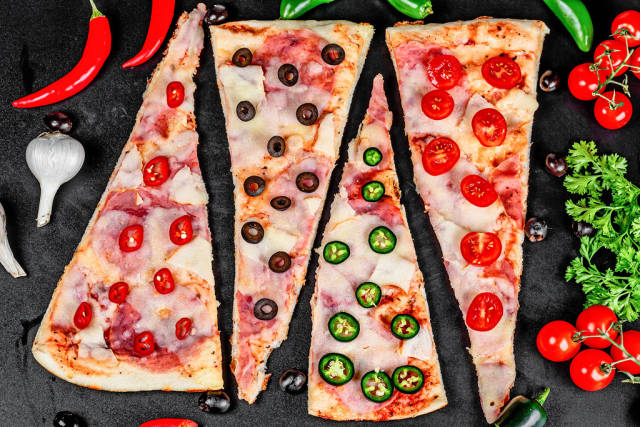 Pizza with ham, mozzarella, tomatoes, olives and hot pepper on a black background, top view