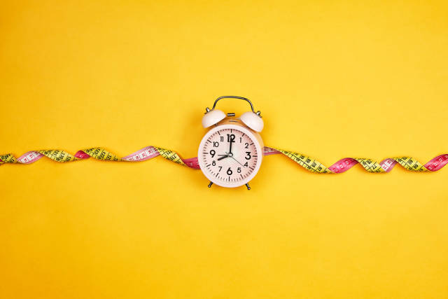 Alarm clock and measuring tape on yellow