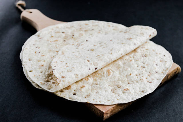 Tortilla wraps on wooden board on dark background
