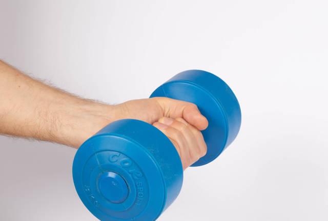 Hand holding blue dumbbell on white background