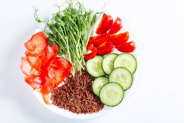 Plate with slices of tomato, cucumber, pickled ginger, brown rice and micro-green peas. Top view