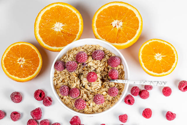 Top view, porridge with raspberries and oranges on a white background