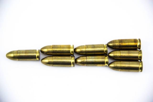 9 mm Pistolenmunition - Patronen in Formation auf weißem Hintergrund