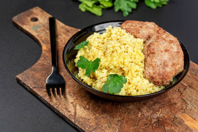 Wheat porridge with fresh parsley and cutlets on a dark background