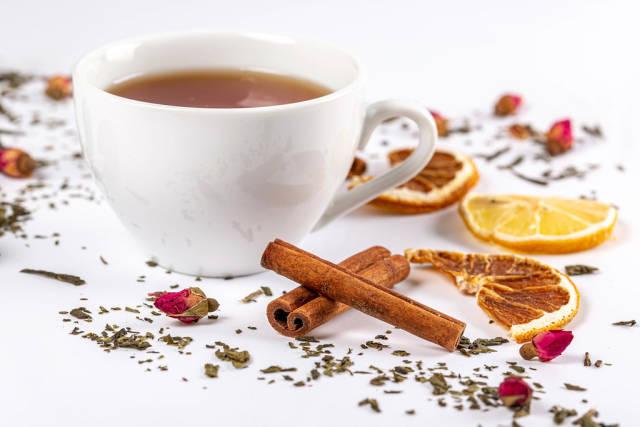 A cup of tea with dried green tea, lemons, cinnamon sticks and flowers