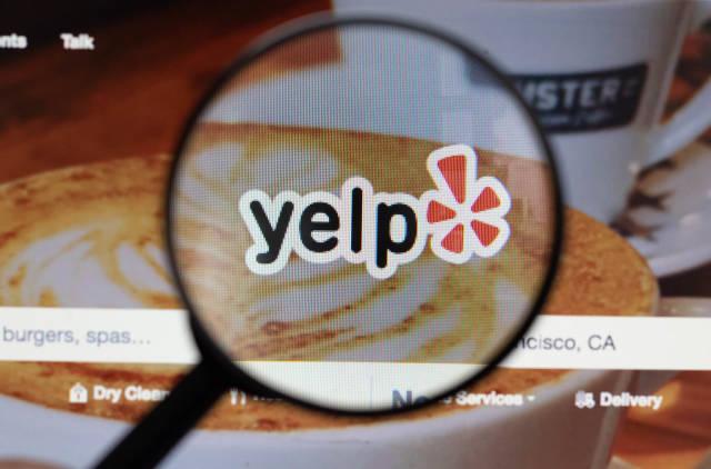 Yelp-Logo am PC-Monitor, durch eine Lupe fotografiert