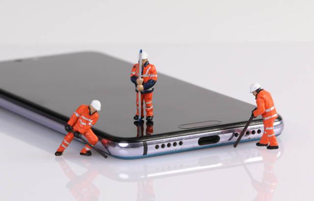 Miniature workers repairing smartphone