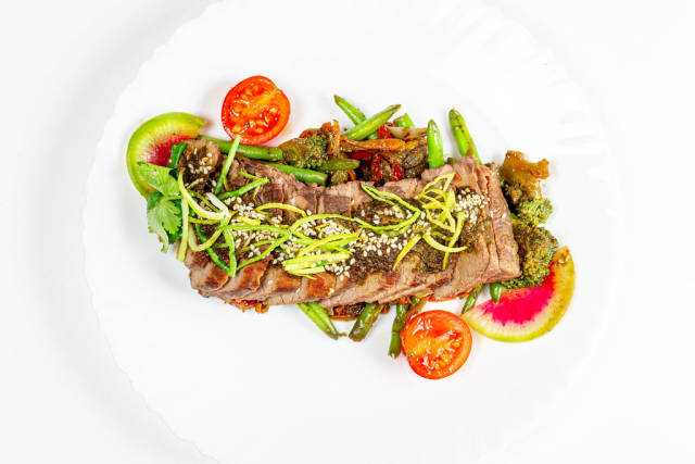 Beef tenderloin with vegetables and spicy sauce on a white plate, top view