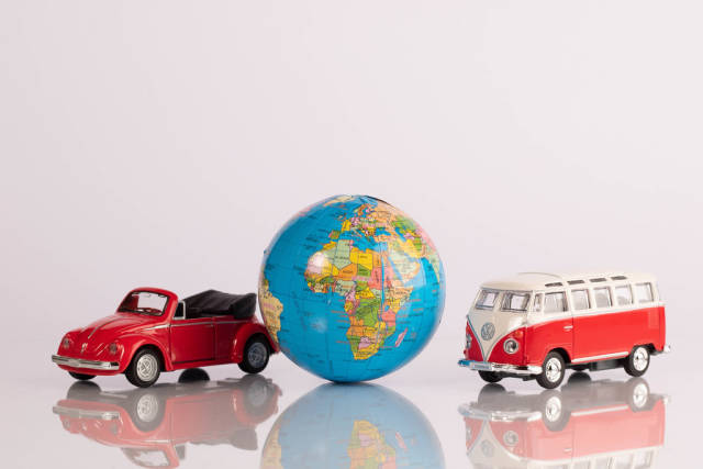 Two red classic cars with globe