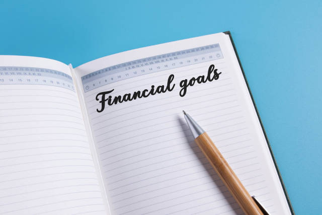 Open notebook with Financial goals text on blue background