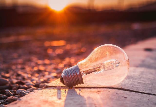 Glühbirne auf dem Boden bei Sonnenuntergang