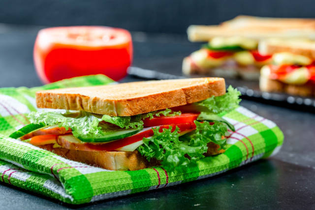 Sandwich with lettuce, tomatoes, cucumbers and cheese on a kitchen green towel
