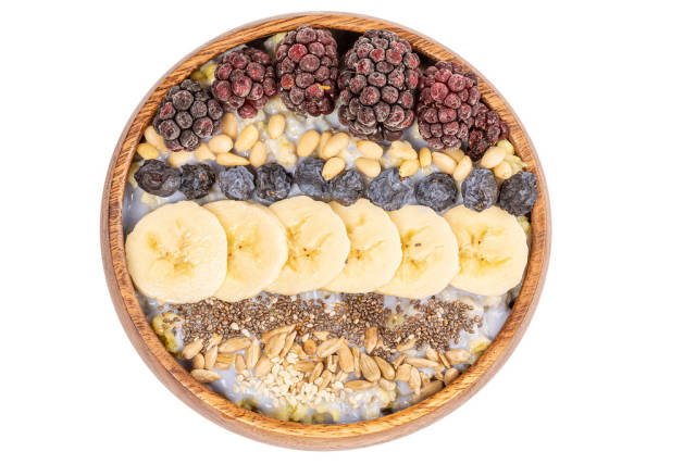 Porridge with different seeds, blackberry, banana, blackthorn and nuts on white, top view