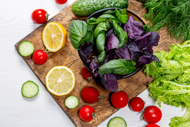 Basil, tomatoes, cucumber and lemon slices with fresh herbs on an old wooden Board