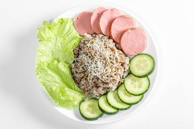 Top view buckwheat porridge with sausage, lettuce, cucumber and alfalfa micro greenery on white background