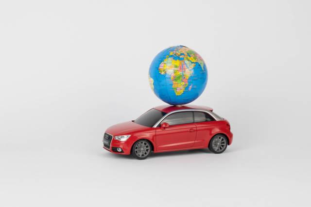 Rotes Spielzeugauto mit kleinem Globus