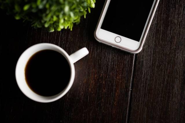 Tasse mit schwarzem Kaffee und IPhone auf einem rustikalen Holztisch
