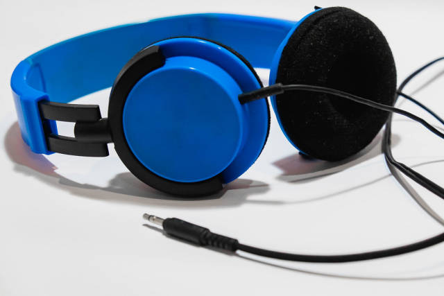 A blue headphones on white surface