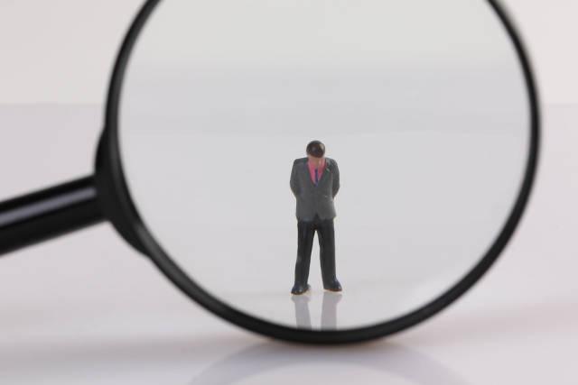 Sad businessman under magnifying glass