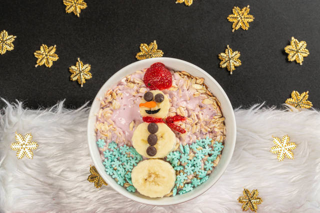 Top view oatmeal with yogurt and snowman made from slices of banana and strawberry