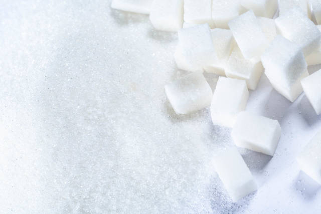 Refined sugar and granulated sugar on white background