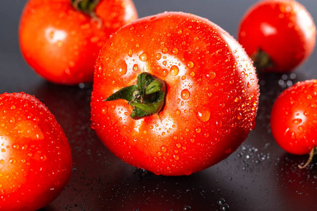 Red fresh tomatoes on a dark background
