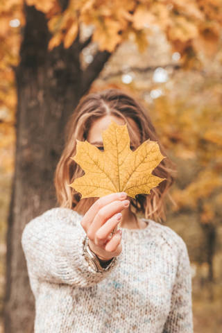 Beautiful autumn portrait of woman with maple leaf in hand