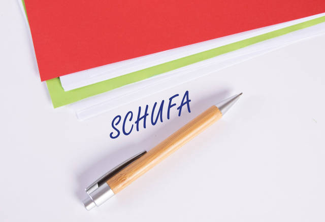 Stack of papers with pen and Schufa text