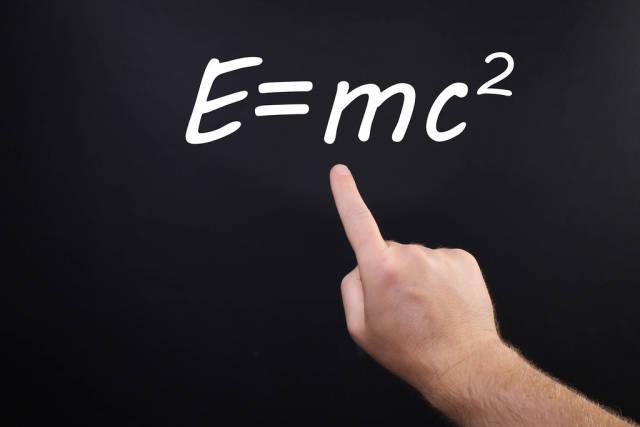 Hand pointing at Einstein Formula E=mc2
