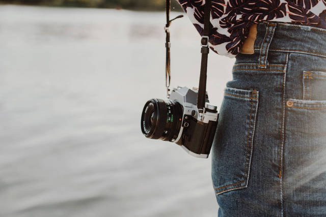 Lifestyle photo of a vintage film camera on a girl. Sea background.