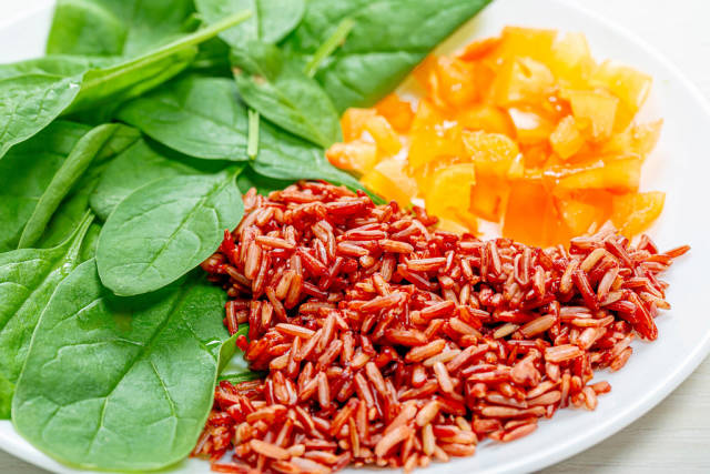 Close up of brown rice with spinach leaves and chopped bell peppers