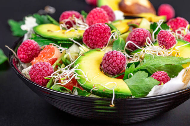 Close-up, salad with avocado and raspberries in a black bowl. The concept of vitamins, taking care of the figure