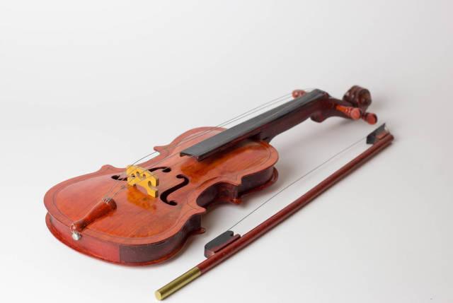 Geige und Geigenbogen auf weißem Tisch